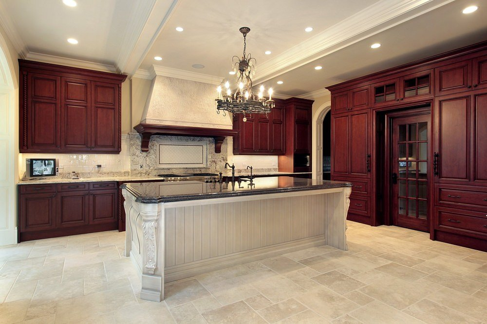 Large kitchen with a glamorous chandelier set on the tray ceiling. The center island with black granite countertop looks so elegant.
