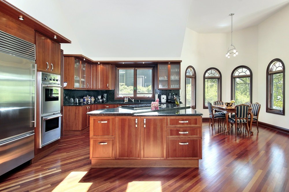 Large classy kitchen boasting elegant flooring, cabinetry and counters. The white walls and high ceiling look perfect together with the kitchen's style.
