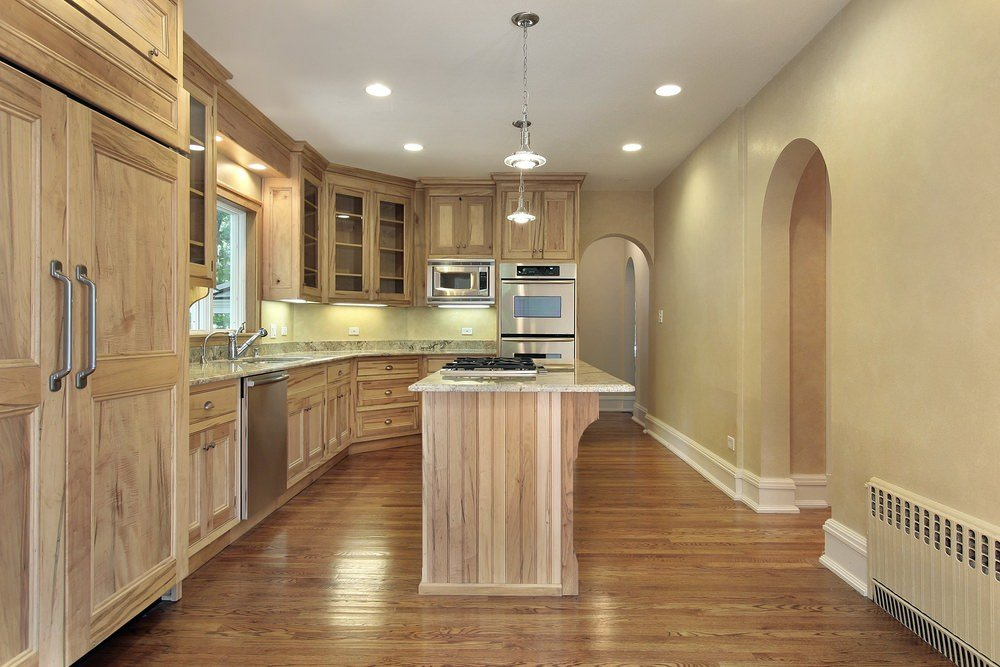 An empty kitchen featuring walnut finished cabinetry, kitchen counters and center island. The area features hardwood floors and beige walls.