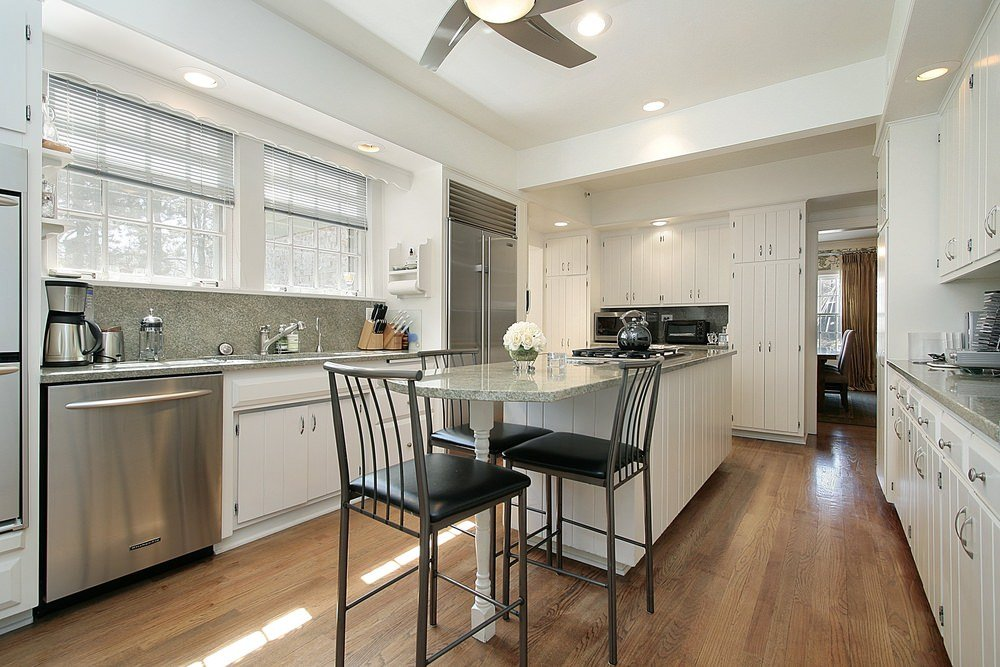 This kitchen features a center island with granite countertop set on the hardwood flooring. The recessed lights are set on the tray ceiling.