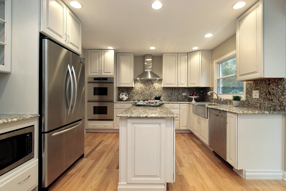 This kitchen boast marble counters and a narrow center island set on a hardwood flooring lighted by recessed ceiling lights.
