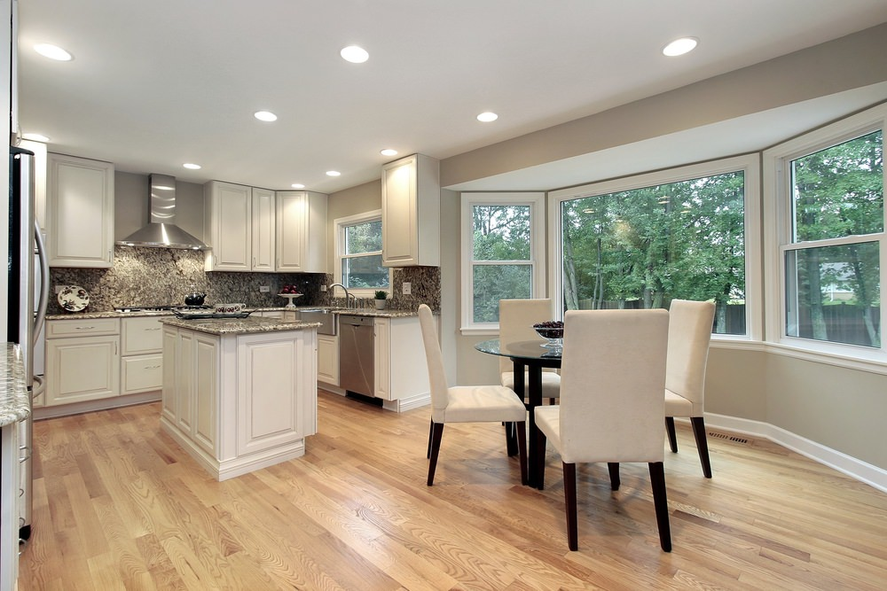 A kitchen featuring stylish kitchen backsplash and granite countertops. The kitchen features a round dining nook.