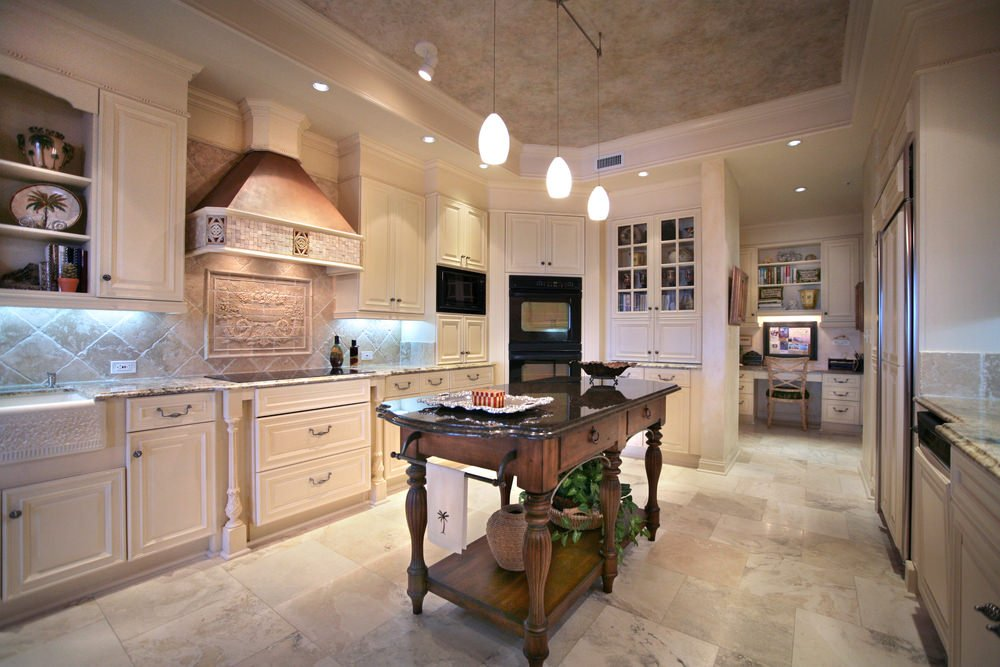 This kitchen features gorgeous pendant and recessed lights set on the tray ceiling. There's a classy center island with black granite countertop set on the marble tiles flooring.