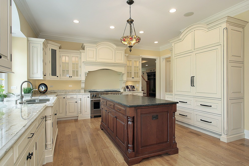 This kitchen features marble countertops on kitchen counters and a black granite countertop on the center island, lighted by recessed and pendant lights.