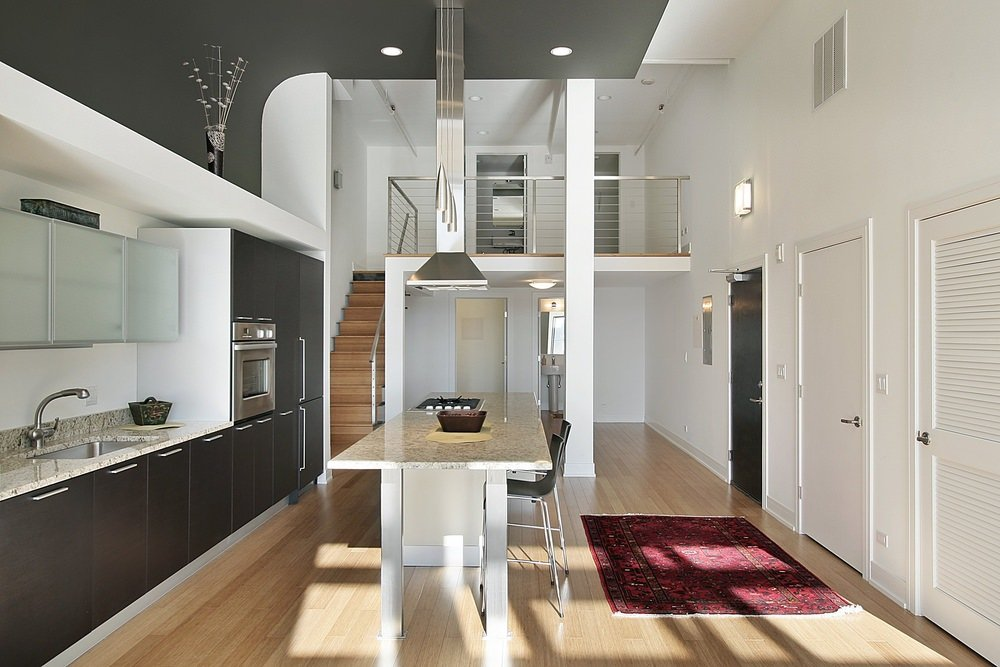 A stylish kitchen featuring marble countertops, hardwood flooring and white walls together with a high ceiling.