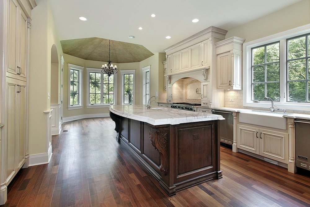 Large galley kitchen with hardwood flooring and a large center island with a marble countertop.