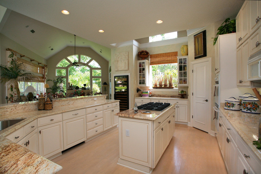 A classy kitchen featuring beautiful countertops on kitchen counters and a nice regular ceiling lighted by recessed lights.