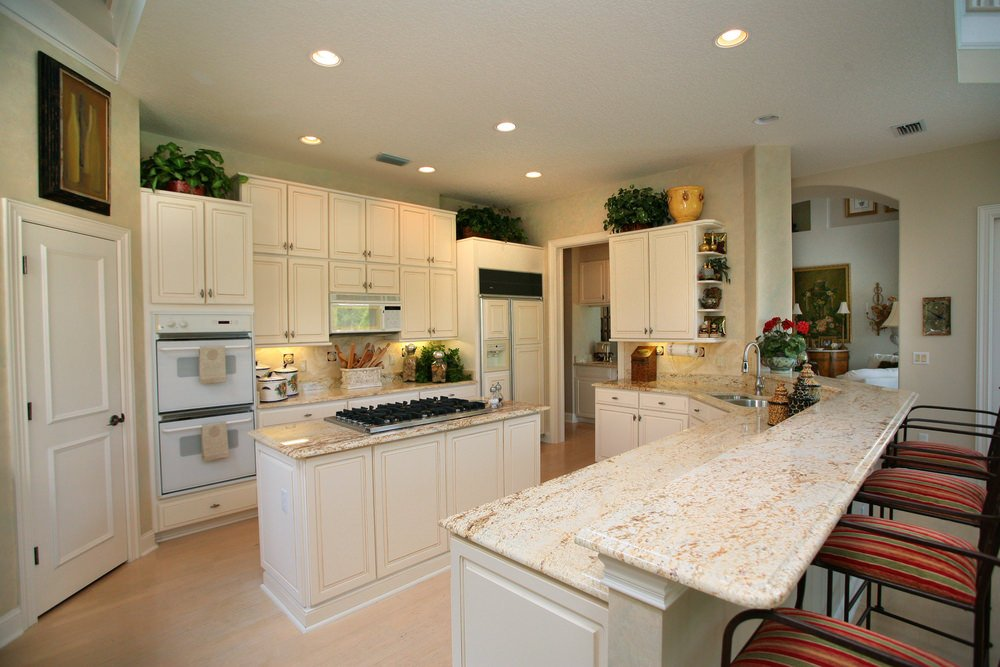 This kitchen features white cabinetry and smooth white marble counters. There's a center island and a peninsula lighted by recessed ceiling lights.