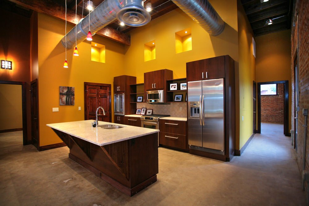 A lovely industrial kitchen with glamorous lighting and beautiful center island with marble countertop.