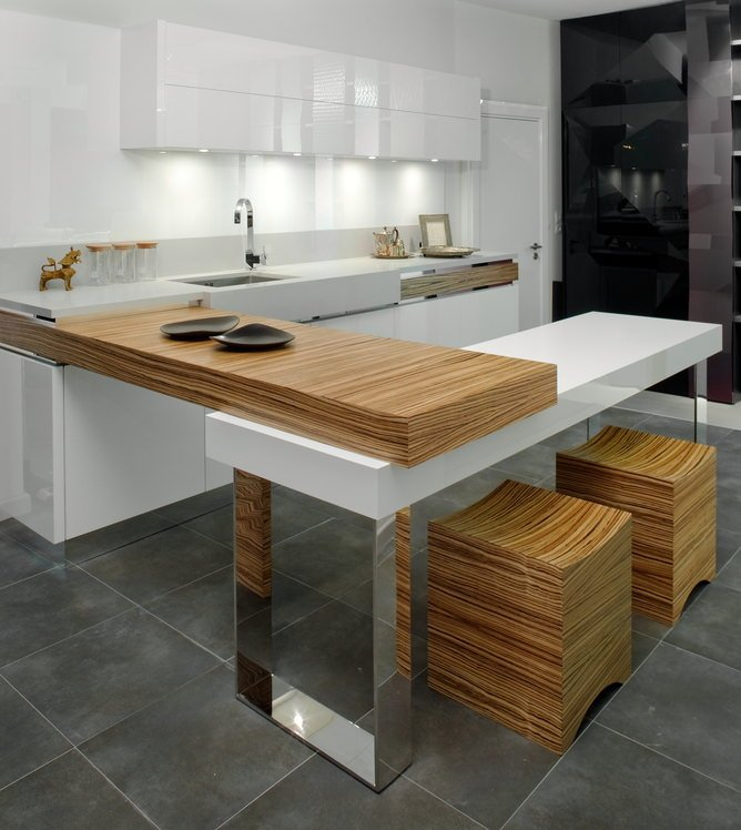 Modern white kitchen with knobless cabinets and a peninsula with wood surface attached to a white table island with mirror legs and a pair of stylish cube stools on gray tile flooring.