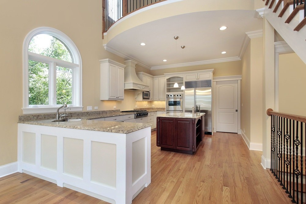 An L-shape kitchen featuring granite countertops on kitchen counters and center island. The room also features beige walls and hardwood floors.
