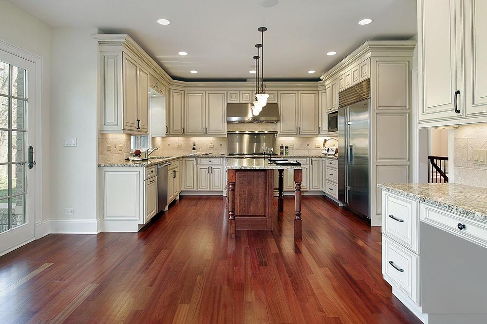 This kitchen features reddish hardwood floors, white granite countertops on both kitchen counters and center island, and recessed and pendant lights.
