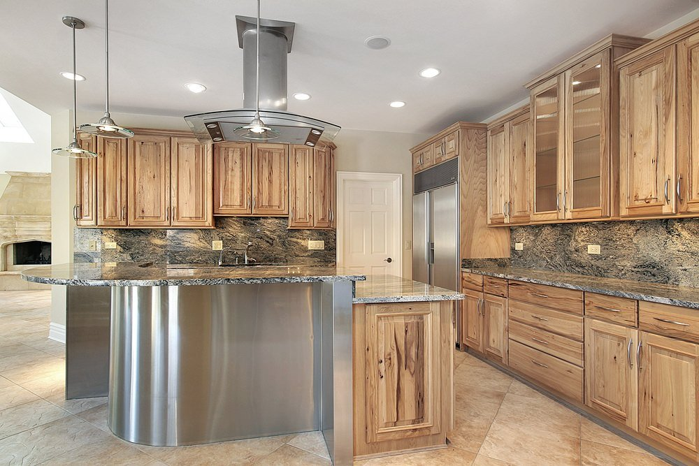 This industrial kitchen boasts walnut finished cabinetry and kitchen counters, matching well with the tiles flooring.