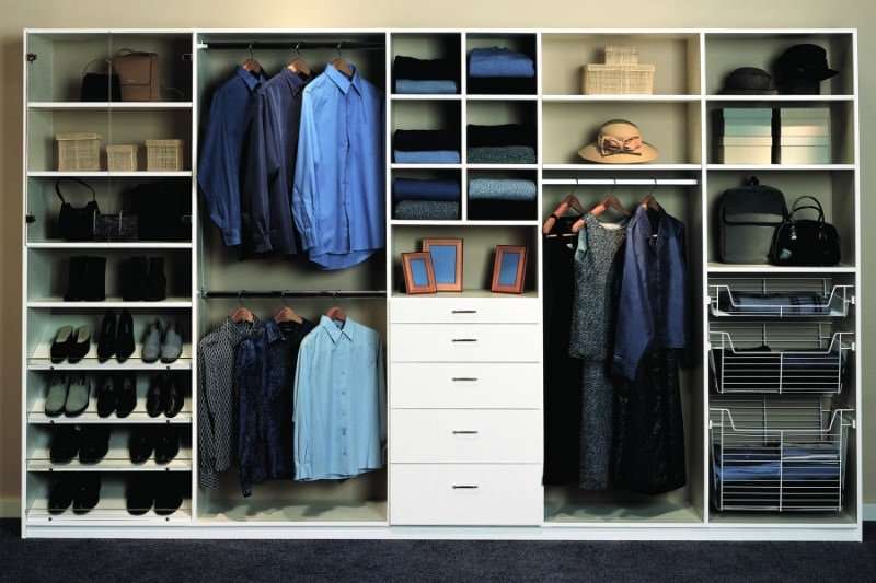 Small bedroom closet featuring a dark carpet flooring and light finished cabinetry and shelving.