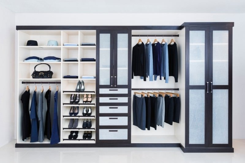 This modern women's closet boasts a stylish espresso finished cabinet frame blending well with the room's white flooring, walls and ceiling.