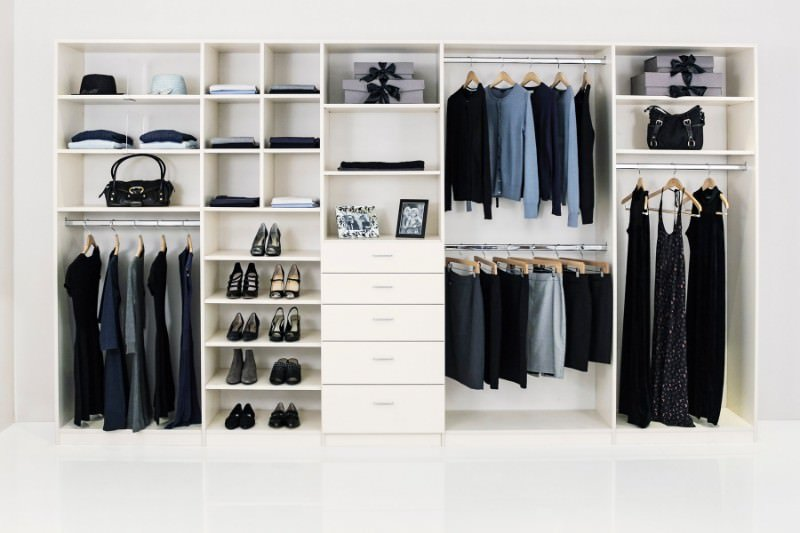 This modern women's closet features white flooring, cabinetry, walls and ceiling. It looks lovely.