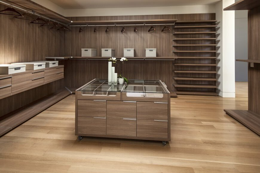 This large modern closet boasts a polished wooden cabinetry, flooring and center island topped by a glass counter.