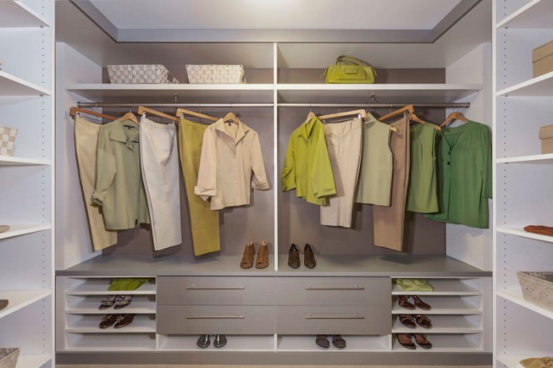 Modern women's closet featuring gray cabinets lighted by recessed ceiling lights.
