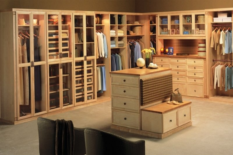 Large bedroom closet featuring walnut finished cabinetry that matches with the center island's top set on a carpet flooring.