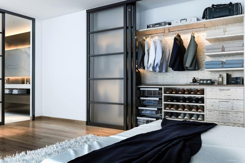 Small bedroom closet for men with a sliding door and light finished cabinetry and shelving.