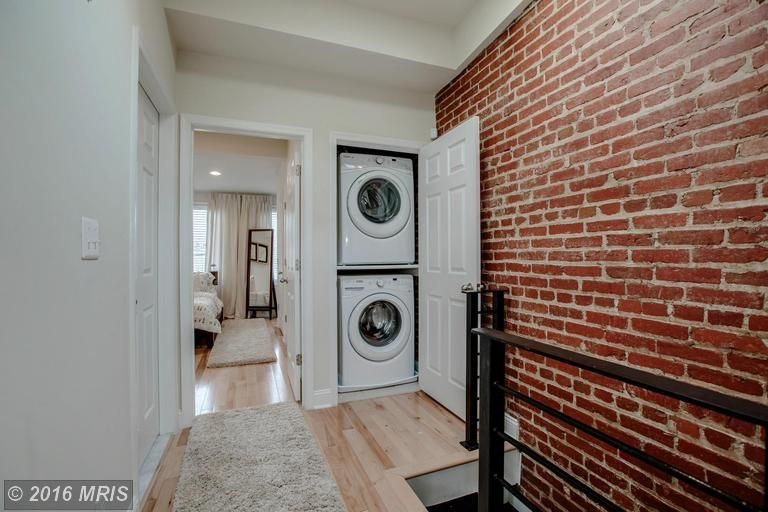 This closet-type laundry is a nice space-saver idea. The addition of the brick wall is just perfect.