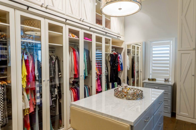 This bedroom closet features white cabinetry with glass doors. The center island boasts a marble countertop lighted by a flush mount lighting.