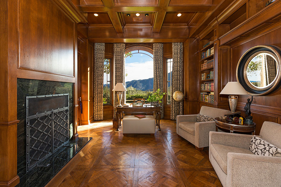 Brown home office with a stunning flooring and an elegant coffered ceiling. The room offers a large fireplace and cozy seats.