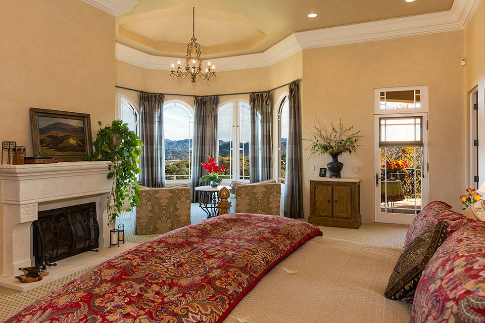 Large master bedroom with its own sitting area near the windows and a fireplace in front of the bed. The gorgeous chandelier hangs from the tray ceiling.