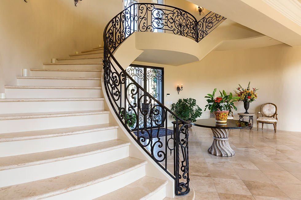 A home entry with a large staircase with beige floors and black railings.
