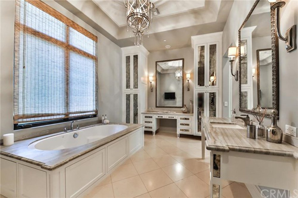 The stylish primary bathroom features two vanities and mirrored storage cabinets along with a soaking tub by the glass window covered in translucent roman shade.