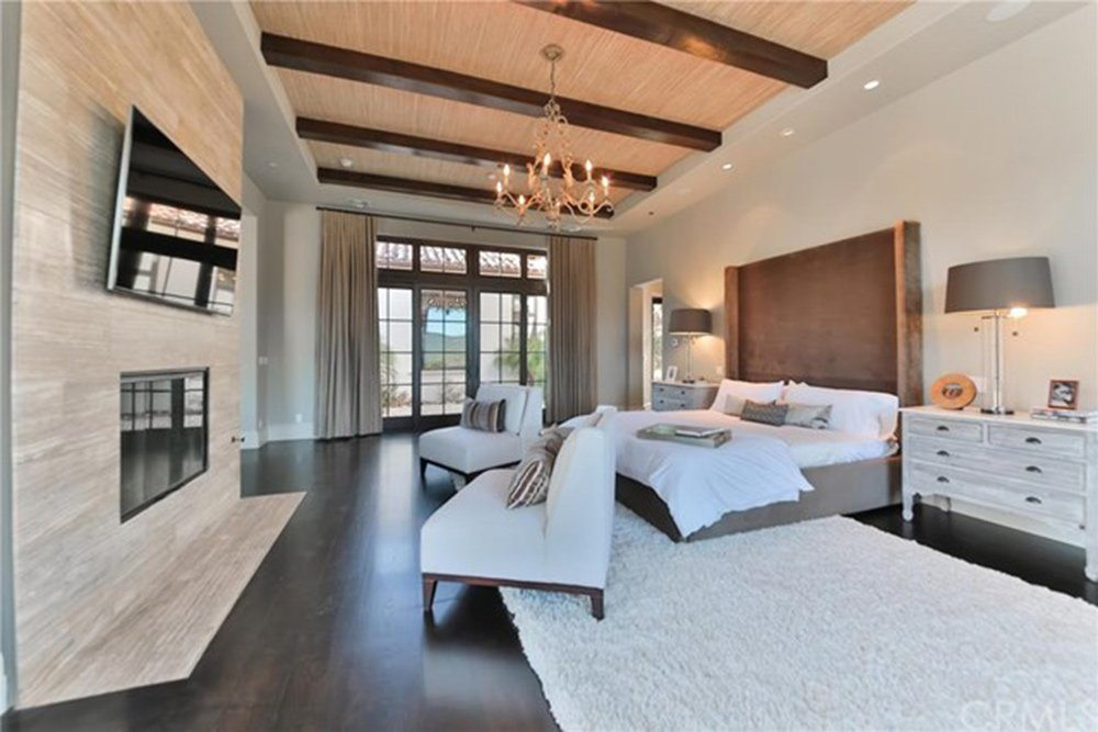 Large primary bedroom with a luxuriously large bed set on the white rug covering the hardwood flooring. There's a fireplace, a widescreen TV and a glamorous chandelier.