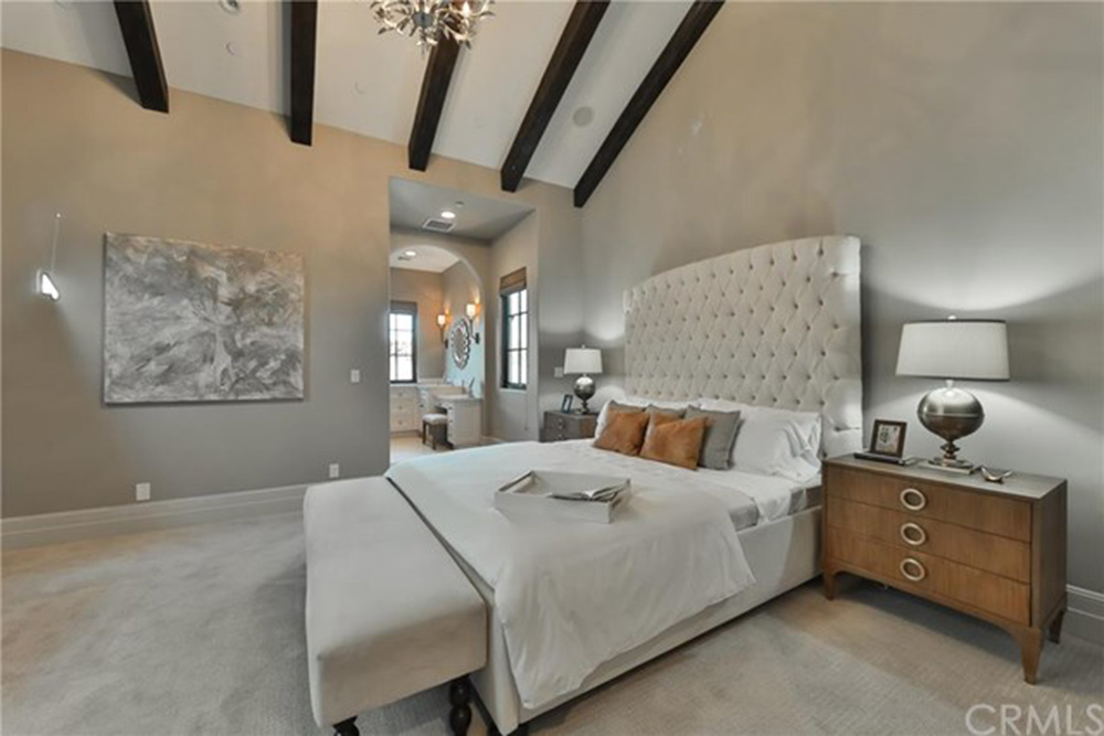 Neutral guest bedroom with a large tufted bed and an open doorway that leads to the vanity area. It has velvet carpet flooring and vaulted ceiling lined with wood beams.