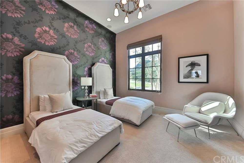 Gorgeous guest bedroom for two with carpet flooring and pastel pink wall mounted with a lovely portrait. The black floral wallpaper creates a nice striking contrast to the room.