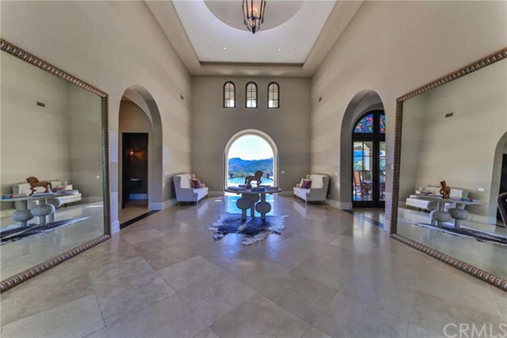 A glamorous foyer with a sense of symmetry with the center table being the focal point of the space. It is surrounded by arched doorways and huge mirrors.