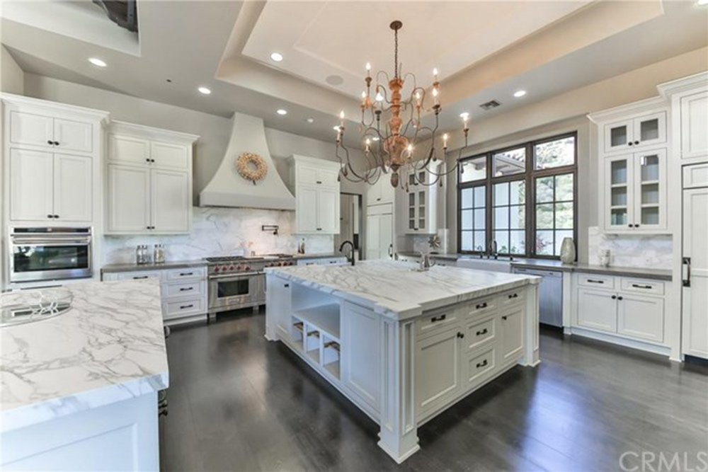 Large kitchen boasting marble countertops on kitchen counters and center island set on the hardwood flooring and lighted by a glamorous chandelier set on the tray ceiling.
