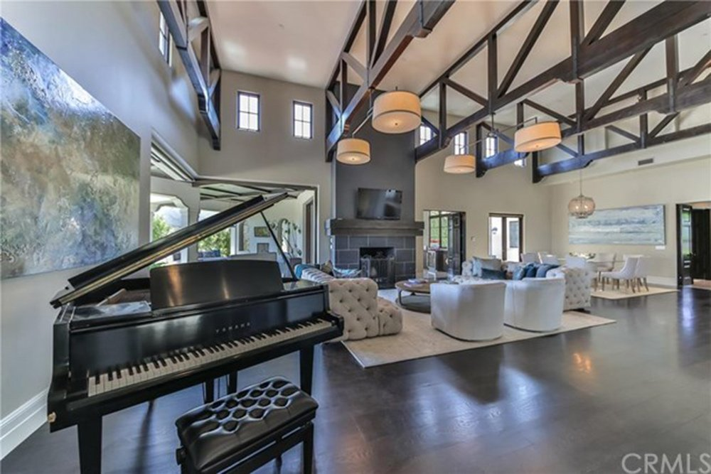 This great room features a high ceiling and dark hardwood flooring along with cozy seats and a fireplace and a black piano on the corner.