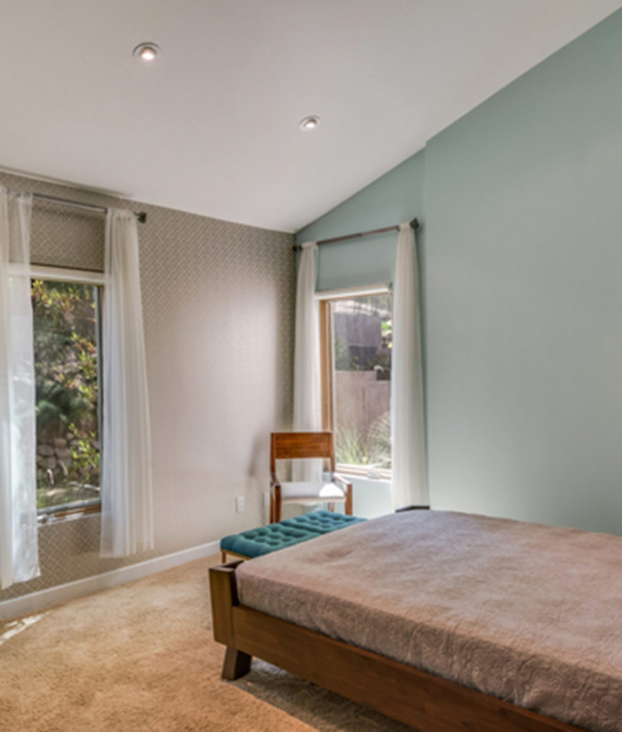 Chris Hemsworth and Elsa Pataky's relaxing guest bedroom accented with green pastel painted and wallpapered walls, carpeted floor and rustic chandelier.