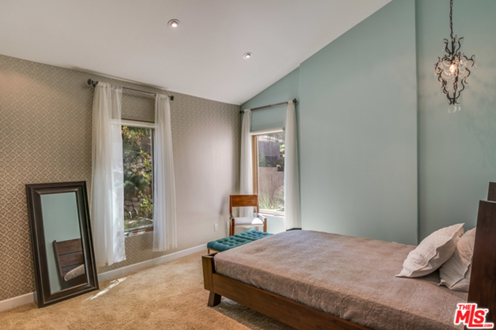 Guest bedroom with green accent wall and vaulted ceiling in Chris Hemsworth's and Elsa Pataky's house.