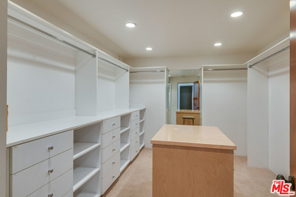 Large white walled walk-in closet with built-in cabinets in Chris Hemsworth's and Elsa Pataky's home.