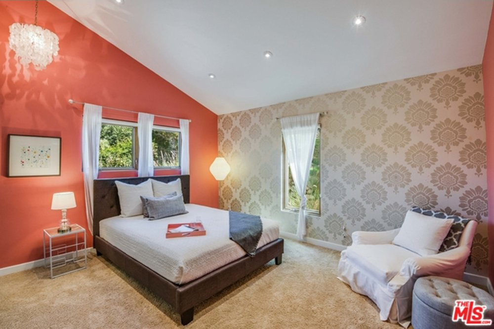 Guest bedroom with salmon accent wall and vaulted ceiling in Chris Hemsworth's and Elsa Pataky's home.