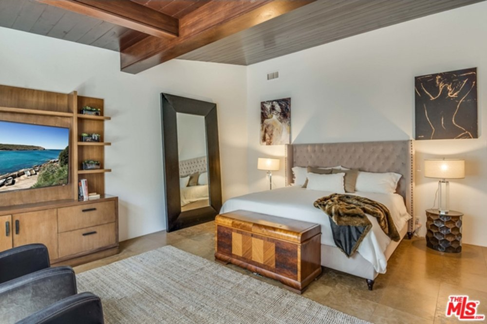 Primary bedroom with TV and wood flooring in Chris Hemsworth's and Elsa Pataky's home.