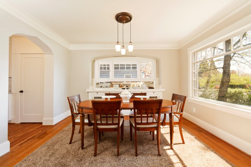 A white archway opens to a bright dining room with an oval dining table and wooden chairs that sit on a brown shaggy rug over rich hardwood flooring.