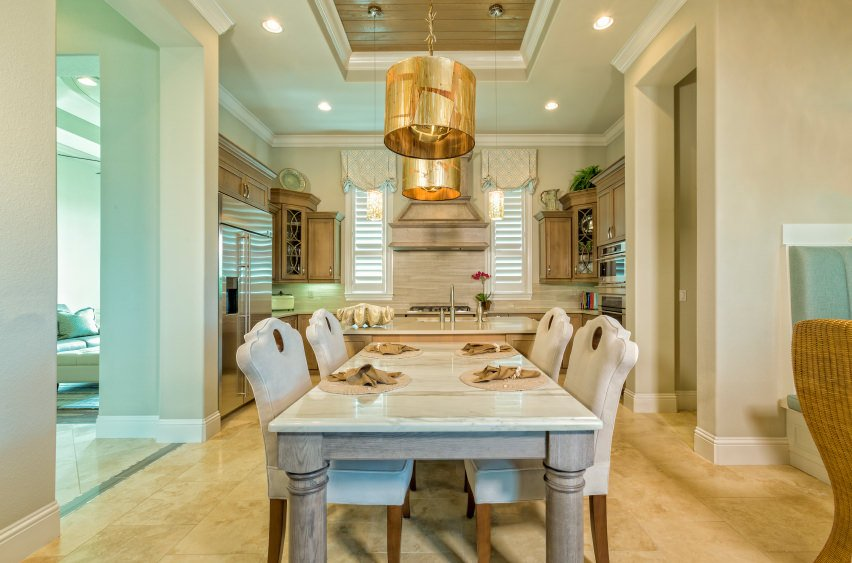 This dining area showcases a marble top dining table and white chairs lighted by a pair of gold pendants that hung from the tray ceiling.