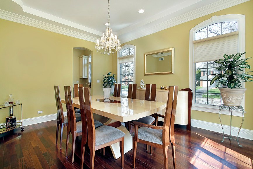 Yellow dining room lighted by a fancy chandelier that hung over a high gloss dining table with stylish wooden chairs fitted with gray cushions.