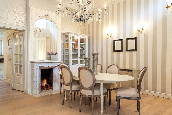 A stylish dining room clad with gray striped and fleur de lis patterned wallpaper. It includes a fireplace fixed below an arched mirror and across the oval dining table with roundback chairs.