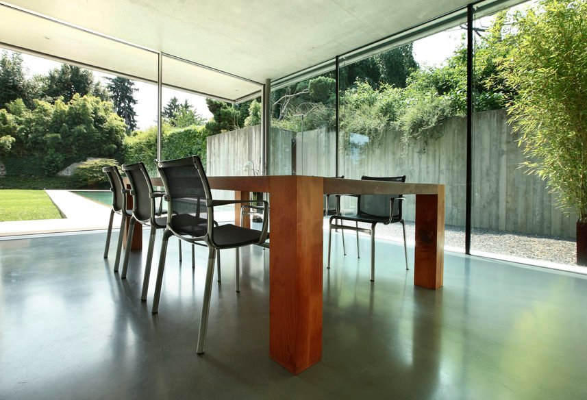 Panoramic windows let you have an al-fresco like dining in this room with a large wooden table and mesh back chairs over concrete flooring. Serene ambiance from the outside along with a sparkling pool completed the look.