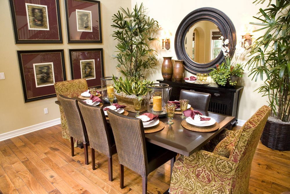 Fresh dining room filled with potted plants and gallery frames along with a round mirror mounted above the buffet table. It has a wooden dining table surrounded by leather and green skirted chairs.