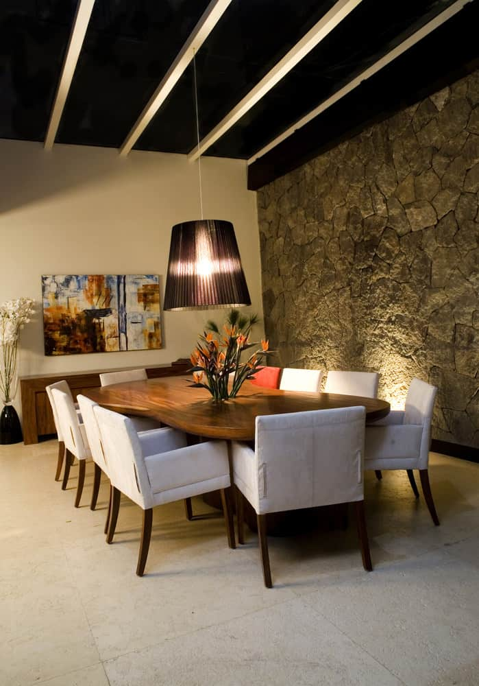 An oversized pendant light illuminates this dining room boasting a stone accent wall and curved dining table with white chairs.