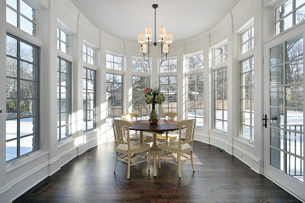 A classy round dining table set on top of the hardwood flooring and is lighted by a gorgeous chandelier.