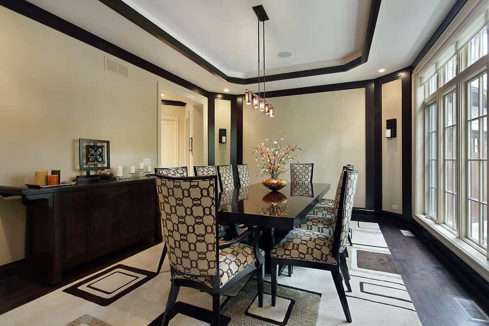 Classy dining room with tray ceiling and dark wood plank flooring topped with a geometric rug. It includes a high gloss dining table topped with an elegant centerpiece and surrounded with patterned highback chairs.
